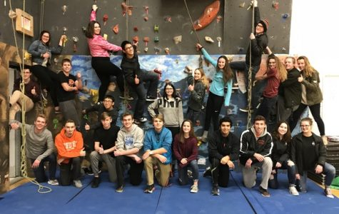 Members of the rock climbing club pose near the climbing wall in the small gym at Central Campus.