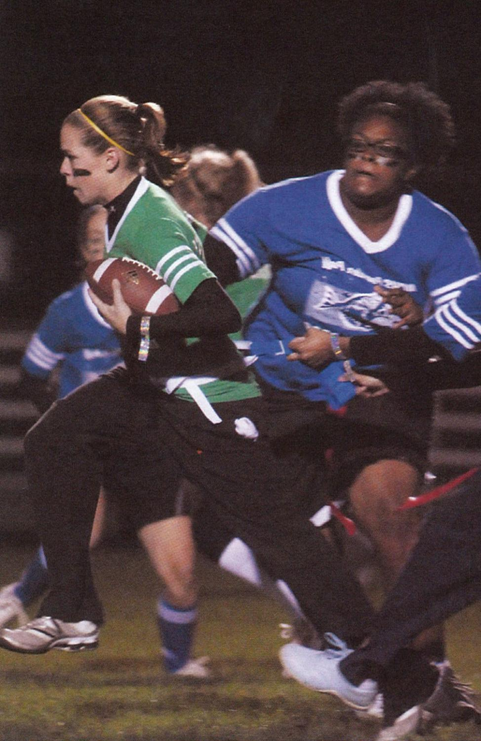 Lyndsay Doyle runs the ball during the 2009 powderpuff game.  Jasmine Stewart attempts to pull the flag.