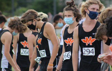 Bryce Harris, Robby Hajduk, Vincent Van Eck and the rest of the varsity boys cross country team line up at the starting line before they race at home against Oswego East on Aug. 29. Runners mask up until seconds before the starting gun goes off. Minooka won the meet, 24-34.