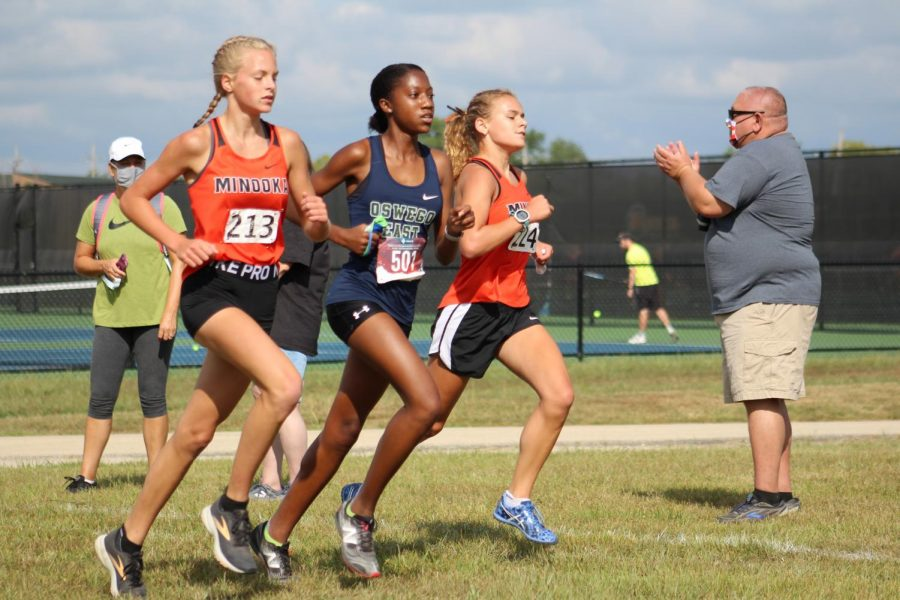 Freshman+Cassie+Fuhrman+and+sophomore+Ella+McColllom+race+against+Oswego+East+on+Aug.+29.